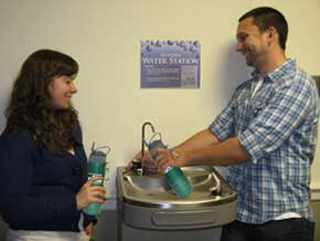 students filling reusable water bottles from a filtered fountain