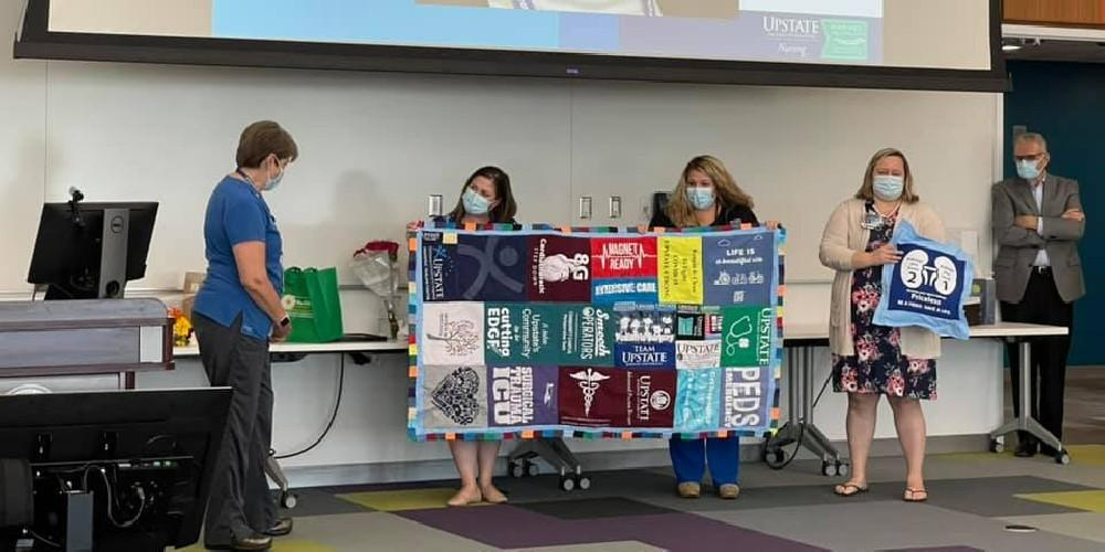 NURSING QUILT: Upstate's Chief Nursing Officer Nancy Page, left, admires a quilt made up of various nursing unit T-shirts. The handmade quilt was one of the many momentos Page received during a reception held in her honor to celebrate her nearly 40-year association with Upstate. Page retires next week.