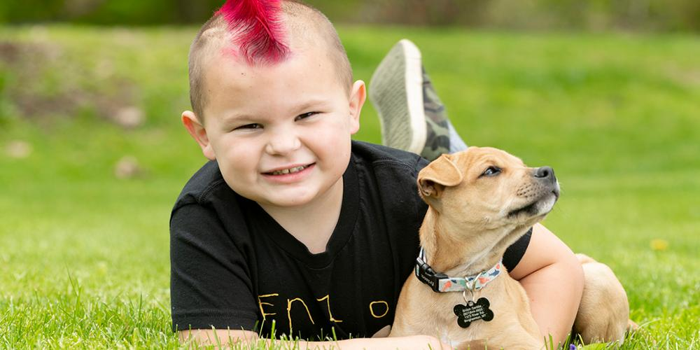 """Enzo Gentile, now 5, wears an """"Enzo Strong"""" shirt while playing with his puppy, Tank. (photo by Robert Mescavage)"""